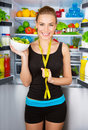 Girl with healthy food portrait of beautiful cheerful holding in hand bowl fresh tasty green salad dietitian recommending eating Royalty Free Stock Photo