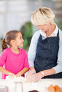 Girl helping grandmother baking adorable little her in kitchen Royalty Free Stock Images