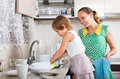 Girl helping mother washing dishes little serious in the kitchen focus on Royalty Free Stock Images
