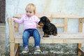 Girl and her dog cute little blond haired toddler sitting on a bench Stock Image