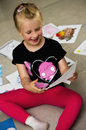 Girl with her drawings on the floor a preschool sitting presenting pictures and paintings done at kindergarten Royalty Free Stock Photos