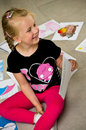 Girl with her drawings on the floor a preschool sitting presenting pictures and paintings done at kindergarten Stock Image