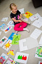 Girl with her drawings on the floor a preschool sitting presenting pictures and paintings done at kindergarten Stock Photos