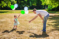 Girl and her father playing with balloons little in park Stock Image