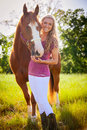 A girl and her horse pretty standing in field with beloved Royalty Free Stock Image