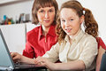 Girl and her mother with laptop at home Stock Photos