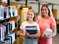 Girl and her mother in library choosing books Royalty Free Stock Photos
