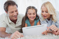Girl and her parents using a tablet lying on carpet Royalty Free Stock Image