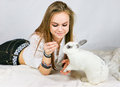Girl with her pet rabbit a teenager plays Stock Photography