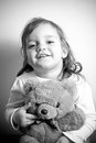 Girl with her teddy bear portrait of a little holding favorite in black and white Royalty Free Stock Photos