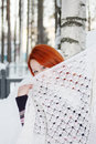 Girl hides face behind shawl near birch at winter cute her forest Royalty Free Stock Photo