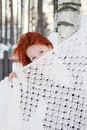 Girl hides her face behind shawl near birch at winter redhead day Royalty Free Stock Image