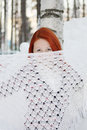 Girl hides her face behind shawl near tree pretty and huge snowdrift at winter Royalty Free Stock Photos