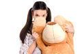 Girl hiding behind the big teddybear piercing beautiful eyes looking over cute Stock Photography