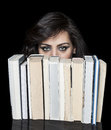 Girl hiding behind book shelf beautiful with deep look a Royalty Free Stock Photography