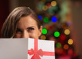 Girl hiding behind Christmas postcard Stock Photos
