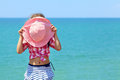 Girl hiding behind a hat pink on background of the sea Stock Photography