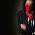 Girl hiding behind a red bandanna beautiful hooligan in tracksuit face is covered in Royalty Free Stock Photos