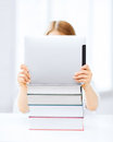 Girl hiding behind tablet pc and books at school education technology internet concept little student Royalty Free Stock Photos