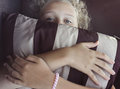 Girl is hiding her face by striped pillow Royalty Free Stock Photo
