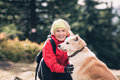 Girl hiking and walking with dog in autumn forest, friendship Royalty Free Stock Photo