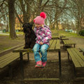 girl with his black schnauzer dog on a wooden bench Royalty Free Stock Photo