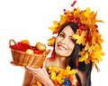 Girl holding basket with fruit wreath of autumn leaves Stock Photo