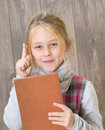 Girl holding a book in her hand Stock Images