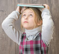 Girl holding books on her head Royalty Free Stock Images
