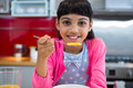 Girl holding breakfast cereal in spoon at home Royalty Free Stock Photo