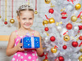 Girl holding a Christmas gift and standing near Christmas trees Royalty Free Stock Photo