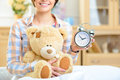 Girl holding a clock and big teddy bear