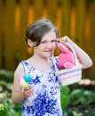 Girl holding eggs and an easter basket with bunny a portrait of a happy little a smile in a dress up a a pink colorful in the Stock Images