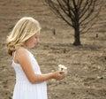 Girl holding flower in baren landscape Royalty Free Stock Photo
