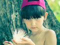 Girl holding flower caucasian kid on the tropical island Stock Photo