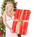 Girl holding  gift box by christmas tree.. Royalty Free Stock Photography