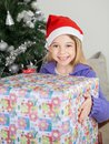 Girl holding gift by christmas tree smiling wearing santa hat at home Stock Photo