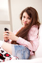 Girl holding a grouch against mobile phone young that disappointed her Royalty Free Stock Photography
