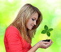Girl holding in hand clover quarterfoil on green background Stock Photos