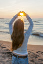 Girl holding hands in heart shape at beach blonde young framing setting sun sunset on ocean Royalty Free Stock Photo