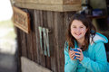 Girl holding hot drink pretty and happy young drinking a in cold outdoor rustic setting Royalty Free Stock Photo