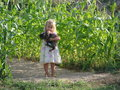 Girl holding kitty yr old clutching a willing cat while standing amongst the garden corn stalks Royalty Free Stock Photography