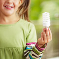 Girl holding light bulb Stock Photos