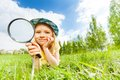 Girl holding magnifier lays alone on green grass Royalty Free Stock Photo