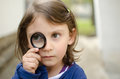 Girl holding magnifying glass serious Royalty Free Stock Image