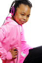 Girl holding mp player listens to music a young african american in jeans her while sitting smiling and listening isolated on Stock Photography