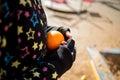 The girl holding the orange.