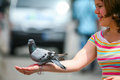Girl holding pigeon barcelona spain june a standing on the hand of a woman on the town square on june th in barcelona spain Stock Photography