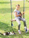 Girl holding rabbit on swing in grey clothes a brown a while a dog is playing with rope Royalty Free Stock Image