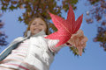 Girl holding red maple leaf in park in autumn smiling close up portrait upward view Stock Image